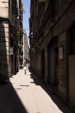 Spain, Barcelona: Street scene with narrow alley in the old town center of the Spanish city at noon with people, tourists, shops, houses, dark shadows and blue sky in the background. July 01, 2018