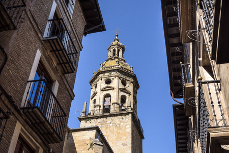 Spain, Puente La Reina, Gares: Steeple of famous old Iglesia del Crucifijo church with skyline of Spanish small town literally named 'Bridge of the Queen', house facades and blue sky in background.