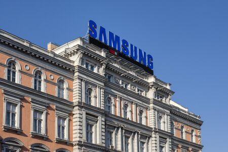 Hungary, Budapest: Big blue Samsung neon sign on a roof top in the city center of the Hungarian capital with blue sky in the background - concept advertisment logo mobile smartphone firm. Feb 07, 2019 에디토리얼