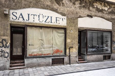 Hungary, Budapest: Street scene with run down house front facade, closed cheese shop (Sajtuzlet) and blinded shop windows in city center of the Hungarian capital - concept business. Feb 05, 2019