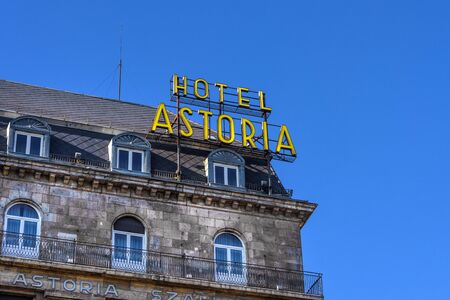 Hungary, Budapest: Big yellow Hotel Astoria neon sign on a roof top in the city center of the Hungarian capital with blue sky in the background - concept advertisment holdiday travel. Feb 06, 2019 에디토리얼
