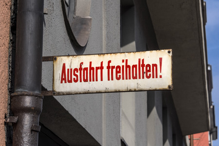 Vintage old classic rusty metal German traffic sign: Keep exit clear! - Ausgang freihalten! - concept gateway traffic street law rule home car information advice close up warning 免版税图像