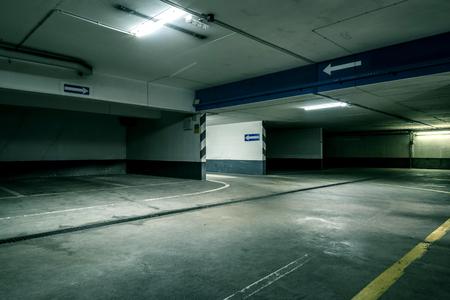 Düsterer moderner Beton Grunge leere unterirdische Tunnelkorridor-Parkgarage mit Reflexionen und neonglühenden Oberleitungslichtern - Konzeptarchitektur unterirdischer Tunnel Gefahr Transport