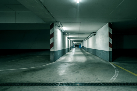 Gloomy modern concrete grunge empty underground tunnel corridor parking garage with reflections and neon glowing overhead tube lights - concept architecture subterranean tunnel risk danger transport