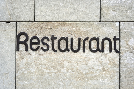 Restaurant sign on an exterior wall of a house - concept food cuisine drink eat hospitality openness culture health business organic Imagens