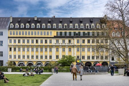 Germany, Bavaria, Munich: People tourists residents on central square Marienhof in the Bavarian capital with yellow original company building of Dallmayr in the background. April 22, 2016