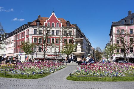 Germany, Bavaria, Munich: People men women relax outdoor in the sun at Gardener Square (Gaertnerplatz) park in the city center of the Bavarian capital. April 29, 2016 報道画像