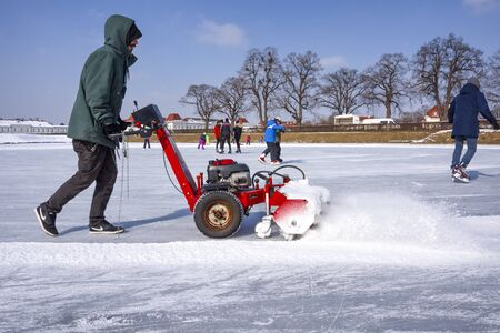 Germany, Bavaria, Munich, Nymphenburg Palace: Man with red snow pusher prepares icy frozen lake for ice skating in a public German park. February 28, 2018 Editorial
