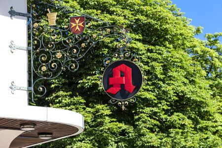 Germany, Heitersheim: Red vintage pharmacy sign with Order of Saint John or Johanniter Order sign - concept German Aphotheke health illness flue pills drugs medication famous brand. June 23, 2018