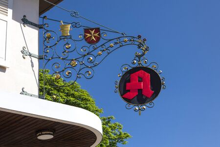 Germany, Heitersheim: Red vintage pharmacy sign with Order of Saint John or Johanniter Order sign - concept German Aphotheke health illness flue pills drugs medication famous brand. June 23, 2018 Stok Fotoğraf - 130633398