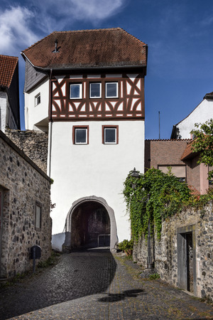 Germany, Rhine-Main area, Hanau, Steinheim: Ancient white half-timbered main gate in the city center of the German town with cobblestone road, old city wall and blue sky - concept travel fortification