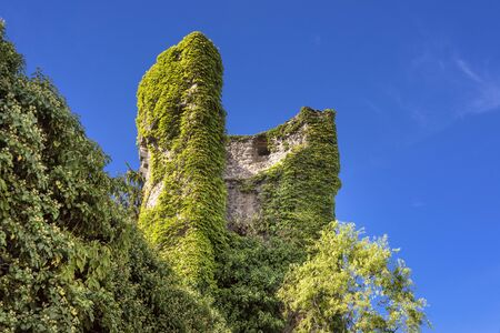 Germany, Hesse, Hanau, Steinheim: Ivy covered tower as part of the ancient city wall in the city center of the German old town with green trees and blue sky in the background - concept history
