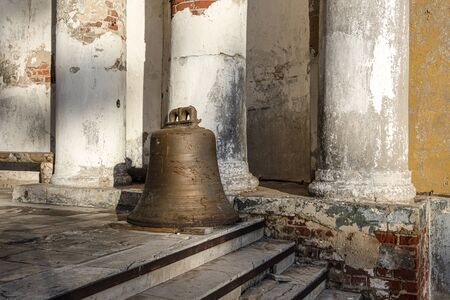 Russia, Vladimir Oblast, Suzdal: Old historic bell at the stairs to the famous yellow bell tower of Rizopolozhenskiy Monastery in the city center of one of the oldest Russian towns with columns.