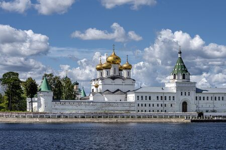 Russia, Golden Ring, Kostroma: Panorama of famous onion domed Ipatievsky Monastery seen from across the Kostroma River near the city center of the Russian town with blue cloudy sky - concept history