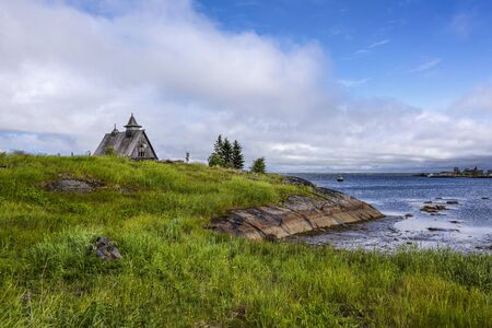 Russia, Karelia, White Sea, near Kem: Old rund down wooden Saint Nicholas chapel in rural remote natural place environment with calm lake water and dark blue cloudy sky - concept lost place outdoor