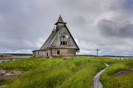 Russia, Karelia, White Sea, near Kem: Old rund down wooden Saint Nicholas chapel in rural remote natural place environment with calm lake water and dark grey cloudy sky - concept lost place outdoor