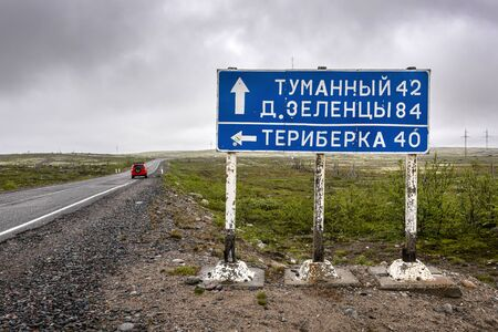 Russia, Arctic, Kola Peninsula, Barents Sea: Street scene with traffic sign to the Russian towns Tumanny, Zelentsy and Teriberka, the old settlement small fishing village with red vehicle, grey day.