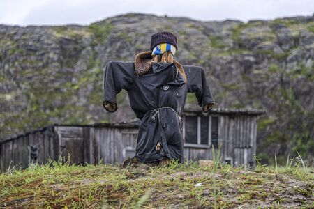 Russia, Arctic, Kola Peninsula, Barents Sea, Teriberka: Scarecrow with uniform coat in front of run down abandoned wooden houses in the city center of the old Russian settlement small fishing village.