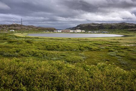 Russia, Arctic, Kola Peninsula, Barents Sea, Teriberka: Aerial view of Lodeiny, the newer part of the old Russian settlement small fishing village with calm lake wate, dark cloudy sky - remote place 版權商用圖片