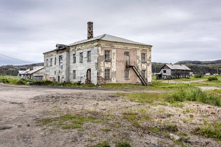 Russia, Arctic, Kola Peninsula, Barents Sea, Teriberka: Run down abandoned houses buildings in the city center of the old Russian settlement small fishing village with sandy road and grey cloudy sky.