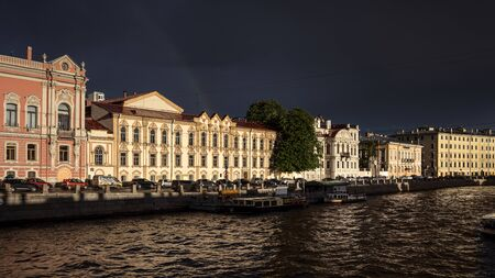 Russia, Saint Petersburg, near Neva river: Row of beautiful renovated apartment houses with boats on Fontanka river in late afternoon midnight sun in the city center of the Russian towns. Jul 08, 2019