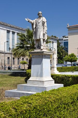 Greece, Athens: Statue of William Gladstone in front of main building of famous UoA National and Kapodistrian University of Athens in the city center of the Greek capital with blue sky. April 24, 2018