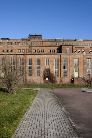 Germany, Saxony-Anhalt, Vockerode: Street view of big old defunct shut down former Vockerode lignite power plant building with brick stone facade, no chimneys and blue sky - concept energy lost place Stock Photo