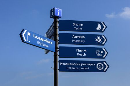 Russia, Black Sea, Sochi: Direction sign post to famous beach, yacht harbor, pharmacy, restaurant in the city center of the Russian town with blue sky in background - information guide. Jun 27, 2019 Redakční