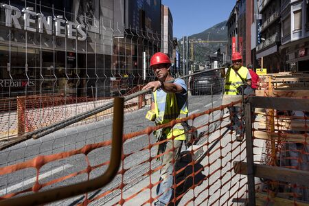 Principality of Andorra, Andorra la Vella: Street scene and two building workers in the famous city center of the Andorran capital with bulding site, skyline, mountains and blue sky. June 25, 2018
