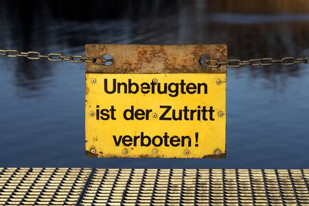 Yellow German sign on a metal chain: No access - no entry for unauthorised persons! (Unbefugten ist der Zutritt verboten!)
