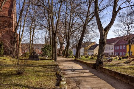 Germany, Brandenburg, Jueterbog: Public park garden of famous Liebfrauenkirche (Church of Our Lady) in the city center of the German small town with leafless trees, pathway, skyline and blue sky.