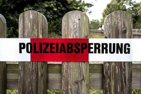 Germany: Red white police cordon (Polizeiabsperrung) on a wooden fence.