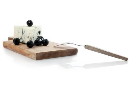 tabla de quesos: de queso azul en la tabla de quesos decorado con aceitunas negras Foto de archivo