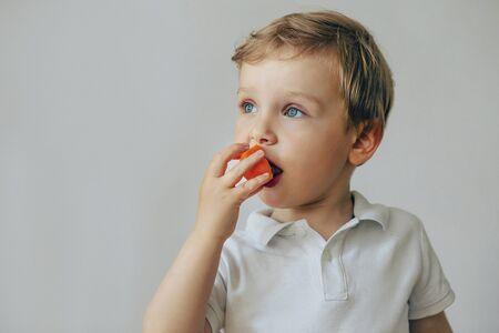 A boy todler in a white T-shirt has an orange fruit.