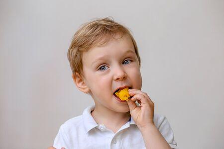 a light boy todler eats an orange fruit.