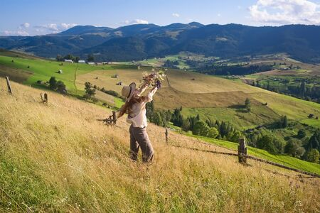a girl with long hair in a straw hat stands on a hill and admires flowers. A girl stands at sunset among the wildflowers on the hillside. In the background you can see the mountains,