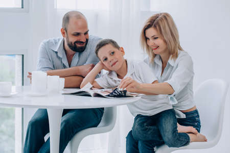 a cheerful family sit at a table and read a magazine. son pondered and looked side