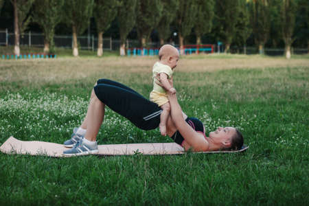 Young woman mom doing exercise sport training with baby in her arms in meadow nature