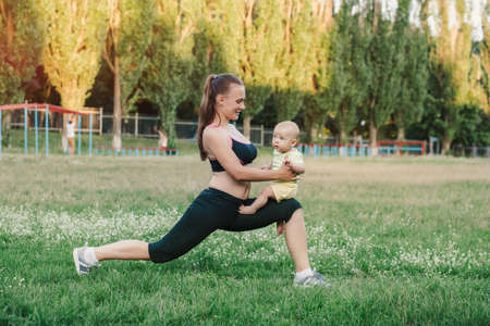 Young woman mom doing exercise with baby in her arms in meadow nature