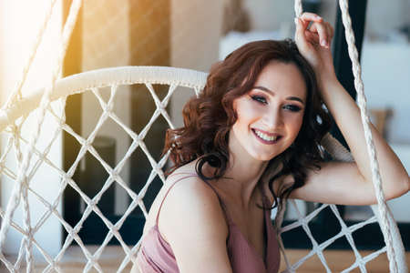 young woman with makeup and hairstyle curls sits in a wicker chair and smiles