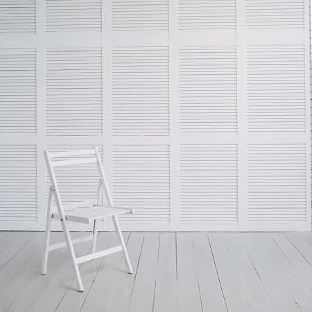a white chair stands on a white parquet against a background of a white wall. Foto de archivo