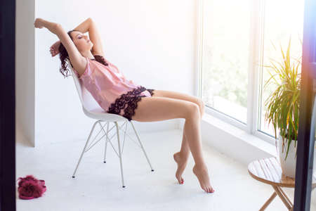 Young woman graceful in pink night underwear and a sleeping mask near the window on a white chair Фото со стока