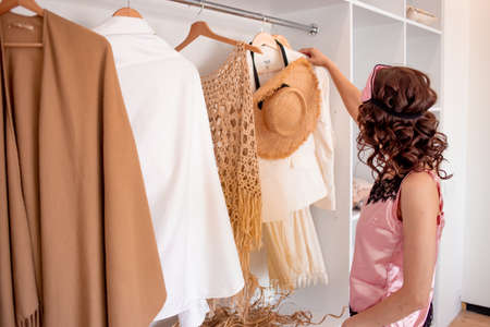 A young woman in pink night underwear and a sleeping mask stands near the wardrobe and chooses clothes