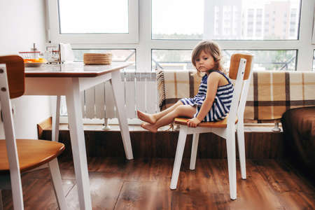 sad child sits alone on a chair in the kitchen. The girl looked down and sits on a stool at an empty table Stock fotó