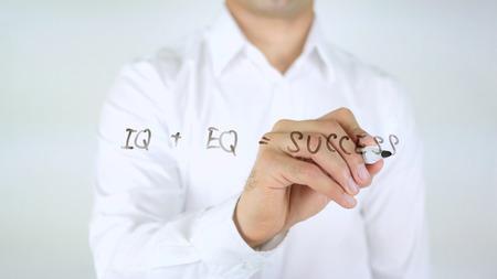 IQ + EQ = Success, Man Writing on Glass Stock Photo