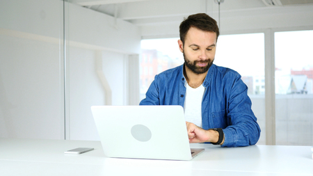 Frustrated Man Watching Time at Work, Want to Go Home Stock Photo
