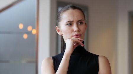 fantasize: Thinking Woman in Office Stock Photo