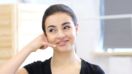 Call Us for Help, Gesture By Woman in Office at Work Stock Photo