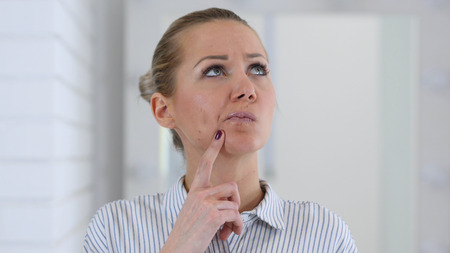 Thinking Young Woman in Office at Work
