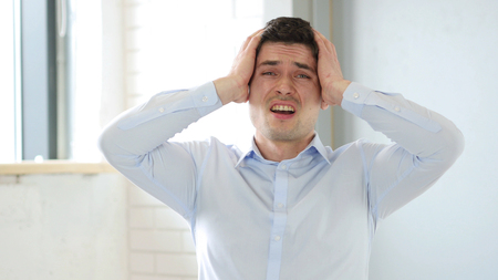 Upset Man Reacting to Failure in Office, Indoor at Work Stock Photo